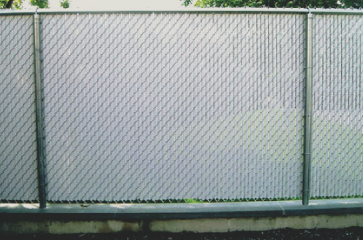 custom-chain-link-fence-built-for-privacy-with-white-vinyl-slats-in-between-the-chain-links