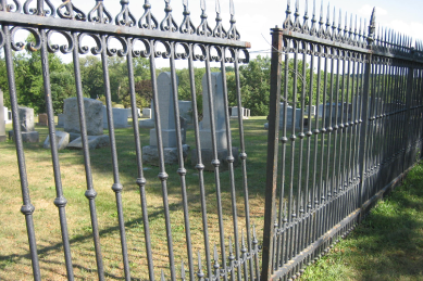 steel-fence-repair-with-one-of-the-ornamental-sections-leaning-and-being-held-together-with-the-non-damaged-section-with-a-wire-or-rope